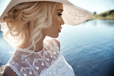 young blond girl with loose curly hair tucked under a straw hat standing lakeside with a white lace top. She is standing and facing to the right