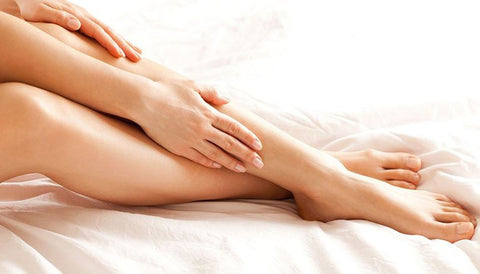 woman rubbing lotion on her legs, image shows bare feet and legs and hands on white linen