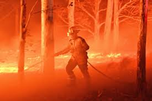 firefighter in Australia wearing mask and standing in orange smoke while battling flames