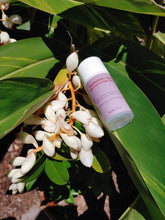 Load image into Gallery viewer, clear airless lotion bottle with light tan and red label and white cap laying on a ginger leaf with ginger flower cluster on left of bottle