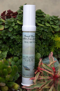 airless bottle of face lotion with label showing beach scene with baby turtles crawling towards ocean, airless bottle laying on a bed of succulents