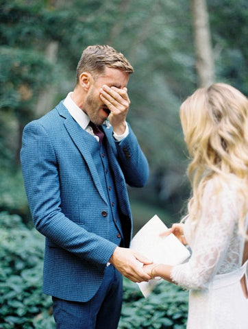 groom crying holding brides hand