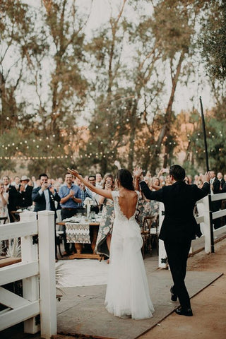 bride and groom making grand entrance to guests at outdoor wedding