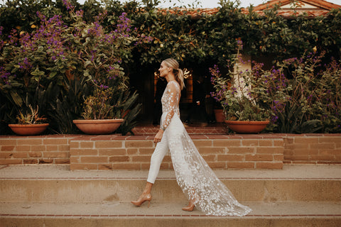 blonde woman in white wedding lace jumpsuit with train