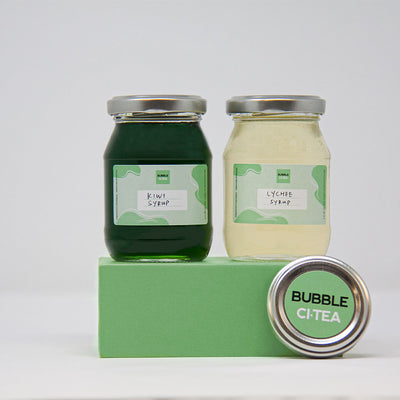 2 smaller Glass jars with kiwi and lychee syrup sitting on a green stand