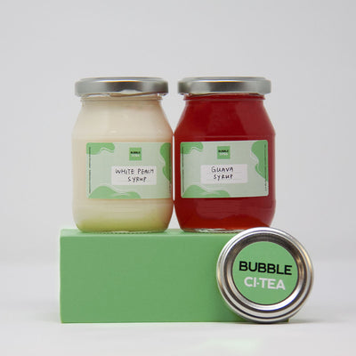 2 smaller Glass jars with white peach and guava syrup sitting on a green stand