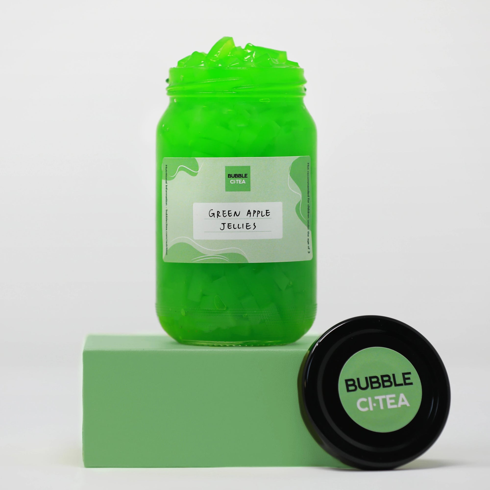 Glass jar with green apple jelly sitting on a green stand