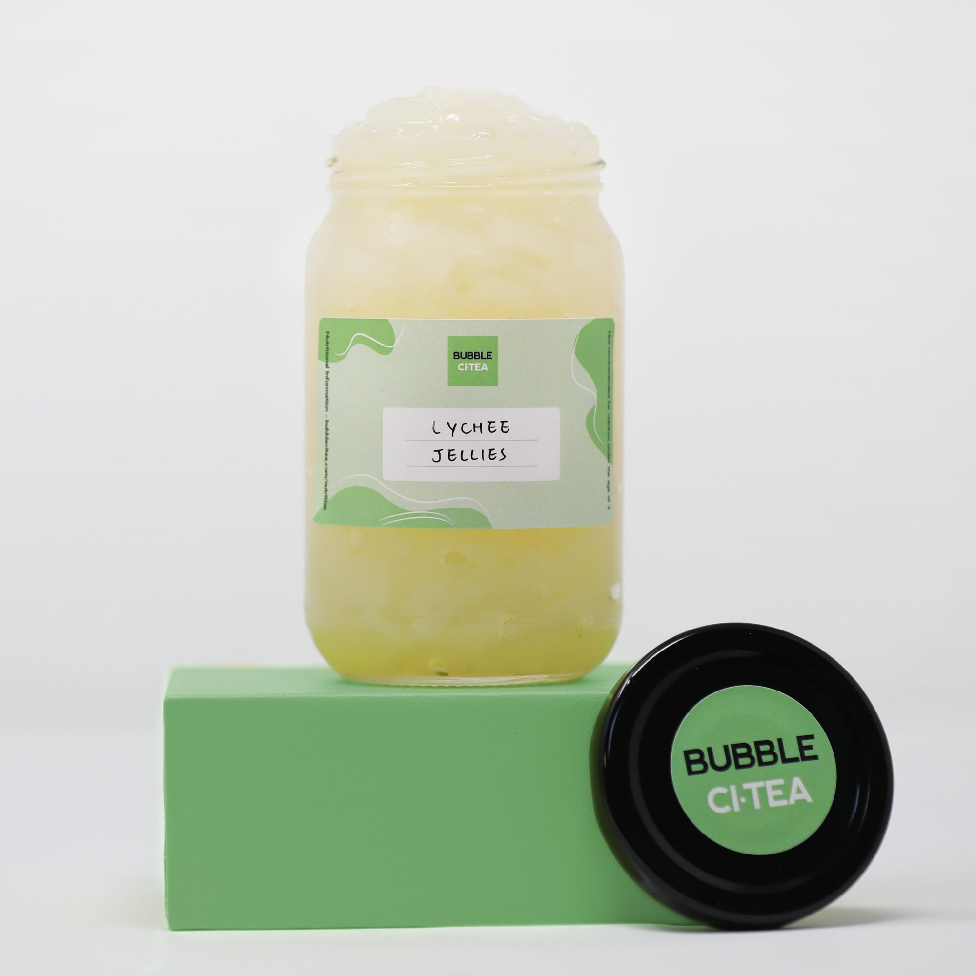 Glass jar with lychee jelly sitting on a green stand