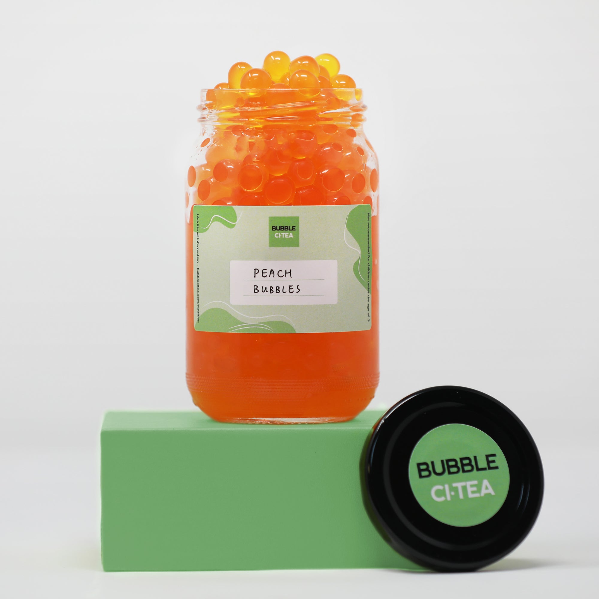 Glass jar with peach popping bubbles sitting on a green stand