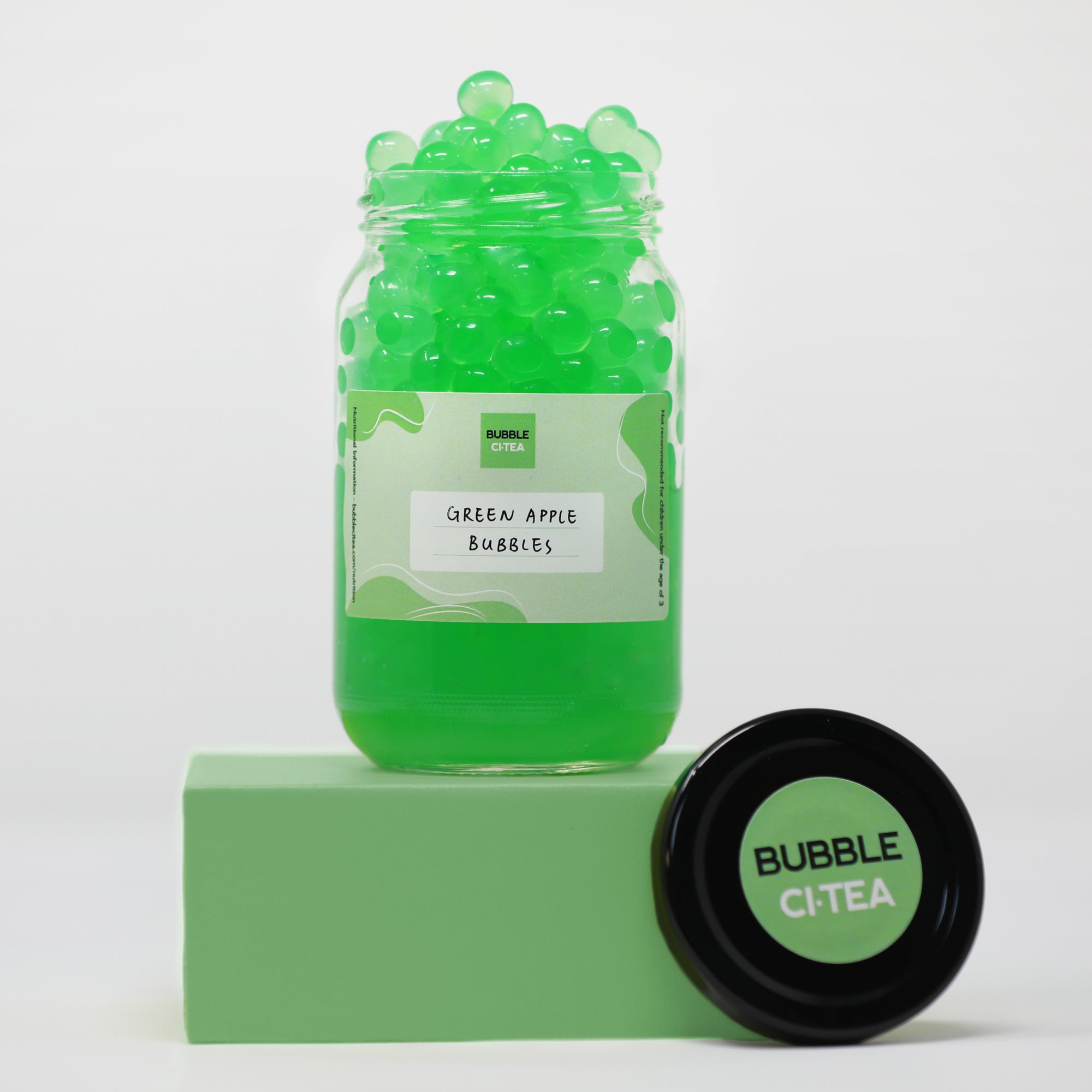 Glass jar with green apple popping bubbles sitting on a green stand