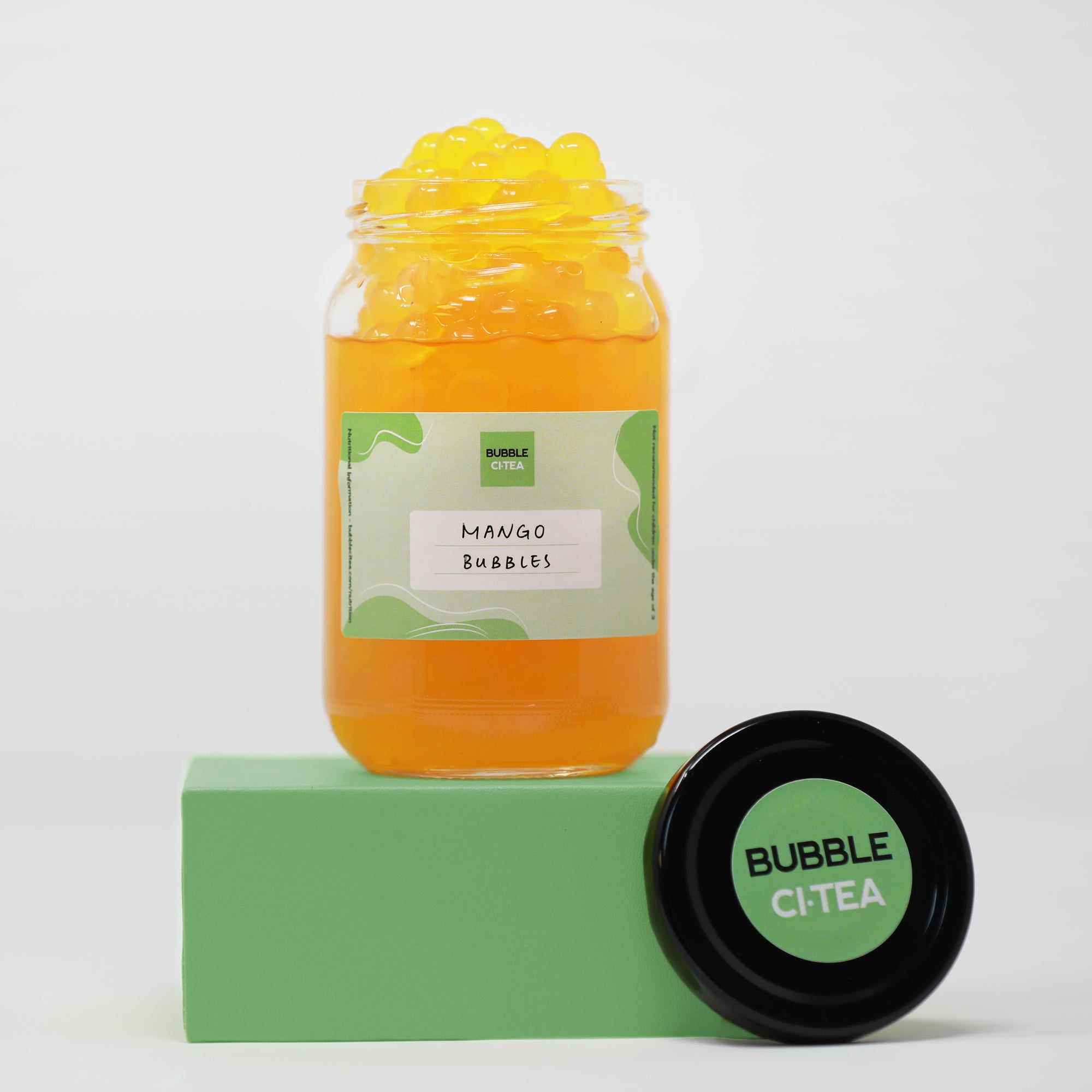 Glass jar with mango popping bubbles sitting on a green stand