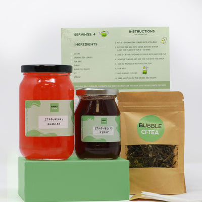 Picture of 1 small jar of strawberry syrup and one big jar of strawberry bubbles sitting on a green stand next to tea leaves and with an instruction card on the back