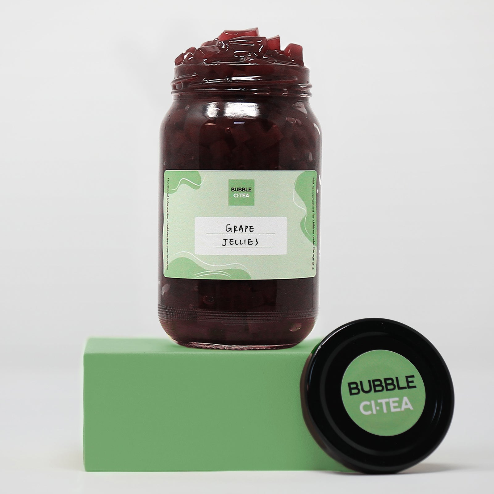 Glass jar with grape jelly sitting on a green stand