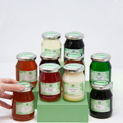 picture of the collection of syrups sitting in different green stands, total of 10 jars