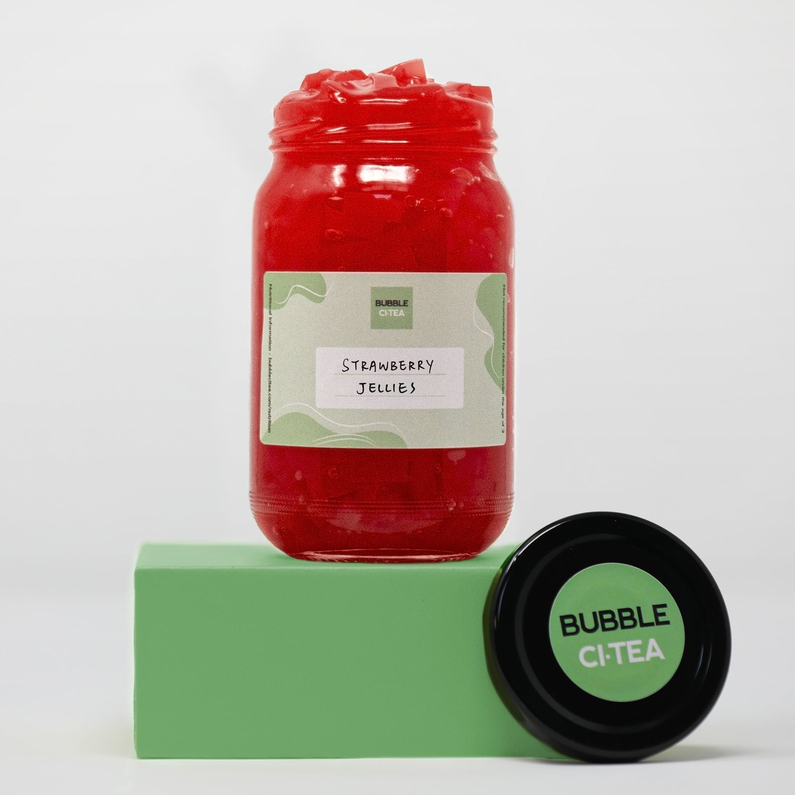 Glass jar with strawberry jelly sitting on a green stand