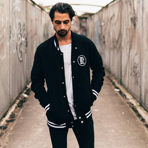 Male model wearing black varsity jacket