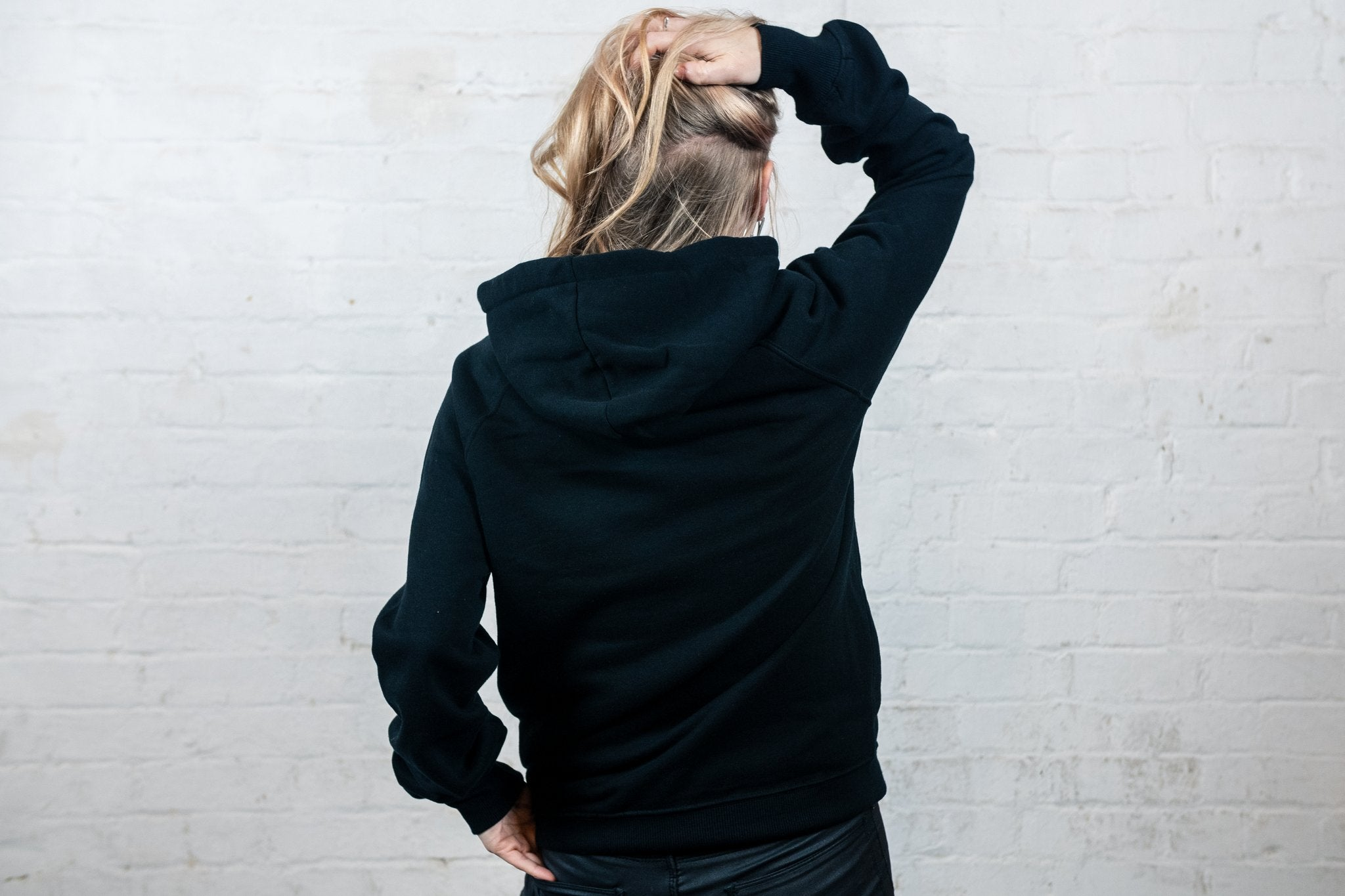 Blonde woman wearing black hoodie, back of hoodie on display