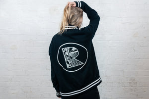 Back of organic cotton varsity jacket in black with white stripe, large Rhetorik logo print worn by female model in studio