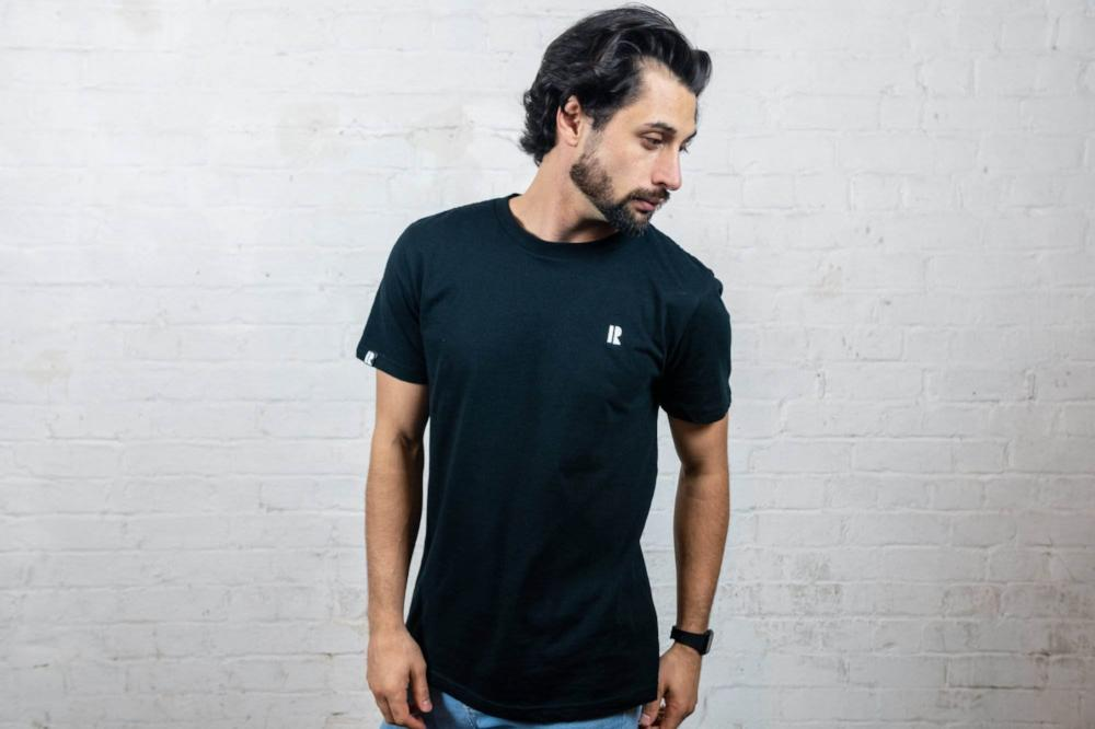 Male model wearing black Rhetorik T-shirt with embroidered logo
