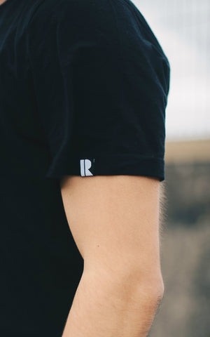 Small sleeve label with Rhetorik logo woven into organic cotton T-shirt in black.