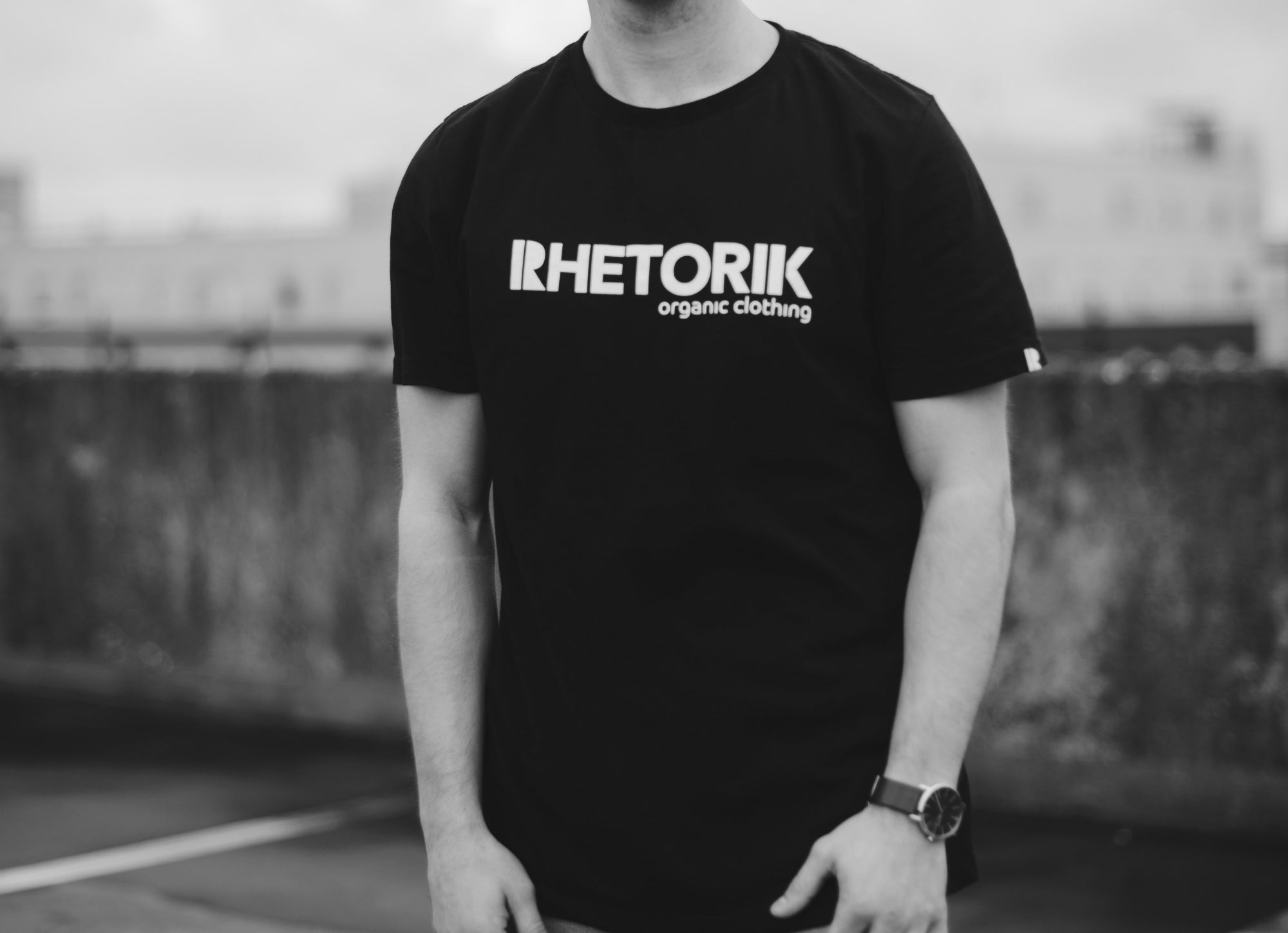 Black t-shirt with Rhetorik organic clothing printed worn by male model, cropped at neck.