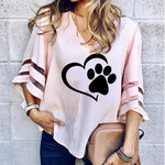 Woman in a pink blouse v-neck t shirt with a paw print and hart with a handbag