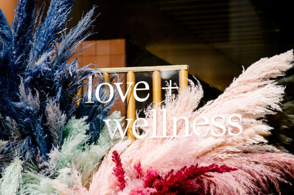 Floral installation window text: love & wellness