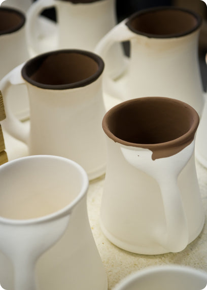large whale tail mugs drying after glazing waiting to be fired