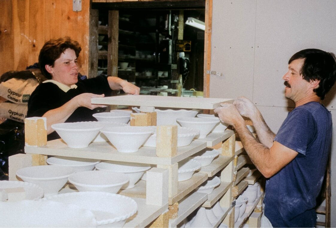 photo of two studio artists loading a pottery kiln shelf by shelf