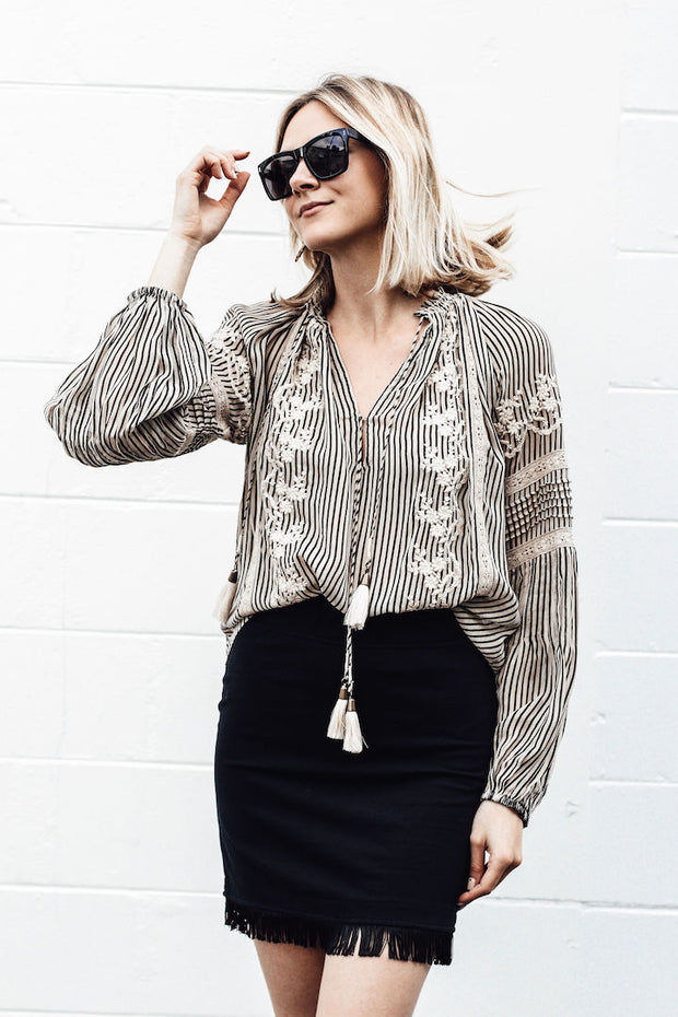 Model wearing Sundays fringe skirt with her right hand about to grab her sunglasses in front of a white block wall view