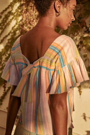 Image of model wearing the SAYLOR Arbor Top in Sherbet, standing outside, back view
