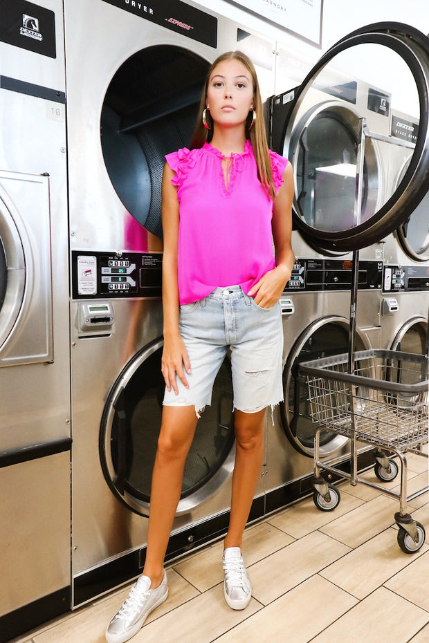 Image of model wearing the AMO Long Lover Boy Cut-Offs standing infront of dryers, full body front view with hand in pocket