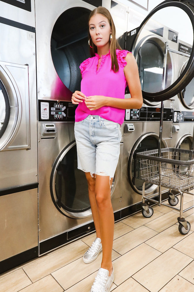 Image of model wearing the AMO Long Lover Boy Cut-Offs standing infront of dryers, full body front view