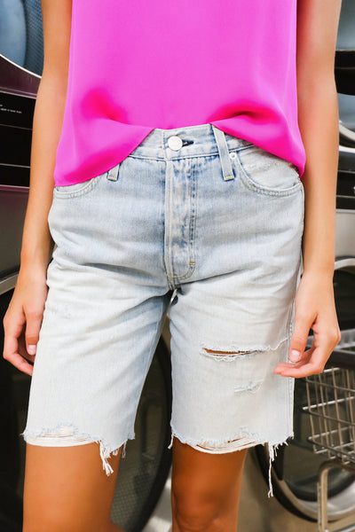 Image of model wearing the AMO Long Lover Boy Cut-Offs standing infront of dryers, close up front view