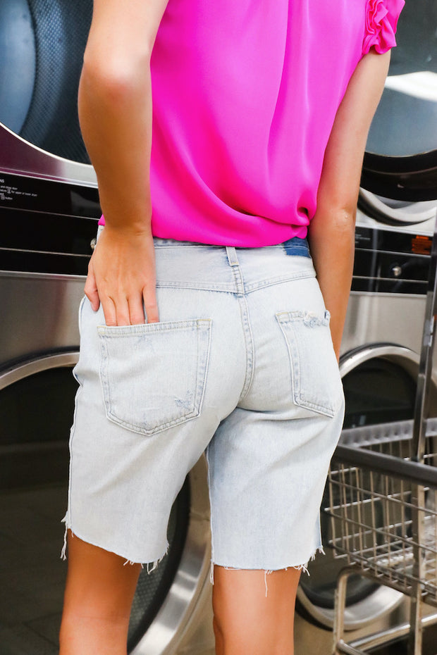 Image of model wearing the AMO Long Lover Boy Cut-Offs standing infront of dryers,  back view