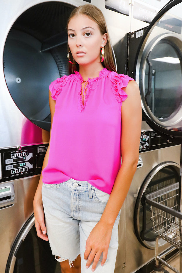 Image of model wearing the AMO Long Lover Boy Cut-Offs standing infront of dryers, front view close up from knees up