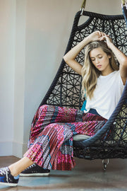 Model wearing Agolde Linda boxy white tee with chevron printed skirt sitting in a hanging chair view