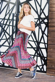 Model wearing Agolde Linda boxy white tee with chevron printed skirt  standing in front of an abstract door