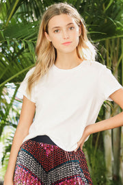 Model wearing Agolde Linda boxy white tee with chevron print skirt outside upclose view