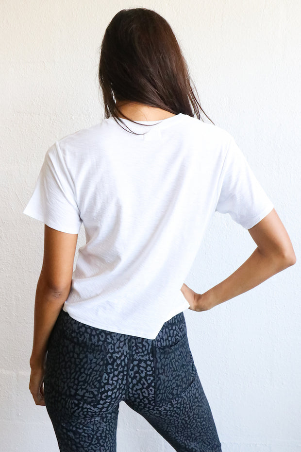 Image of model wearing the NATION LTD Vote Tee standing infront of white wall, back view