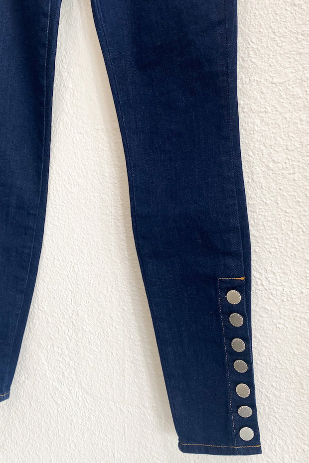 Image of the L'AGENCE Piper H/R Skinny hanging on hanger against white wall,  close up of button detail