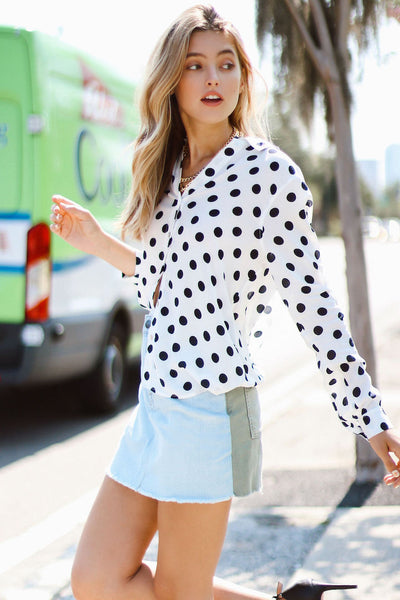 Model walking on  sidewalk wearing le mini skirt cargo mix with polka dot top side view
