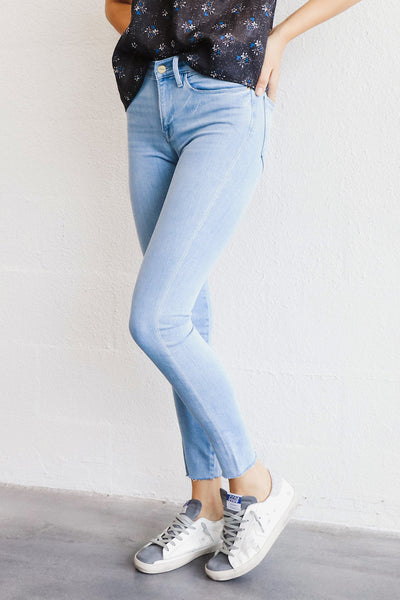Image of model wearing the FRAME Le High Skinny Raw Hem standing infront of white wall, front view close up of legs with one leg bent