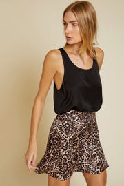Image of model wearing the NATION LTD Birdie Skirt, standing infront of tan background, front view