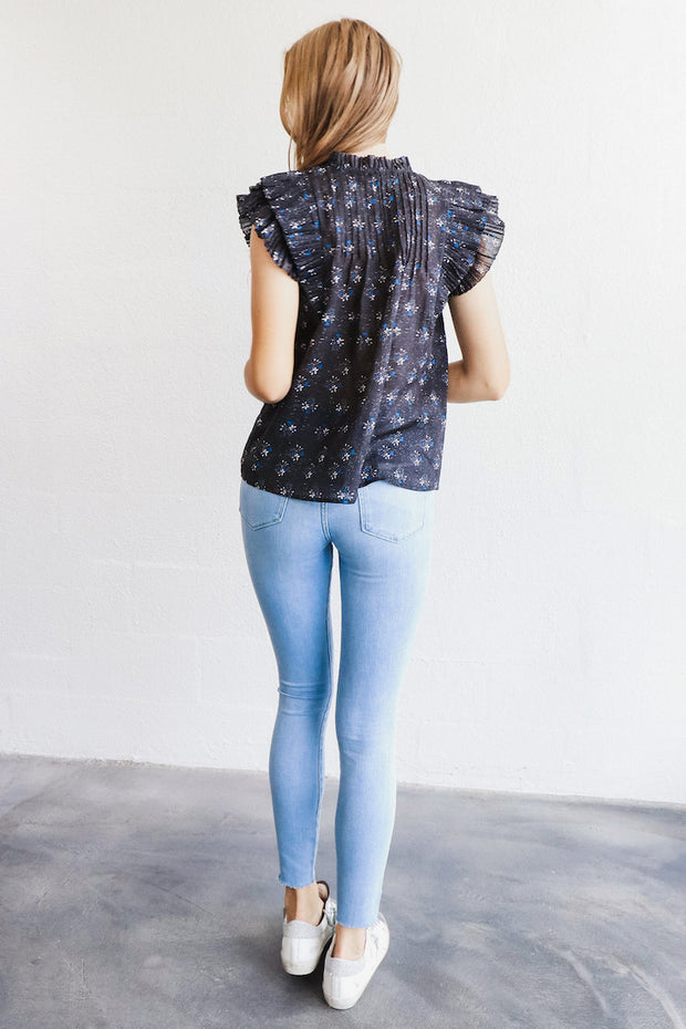 Image of model wearing the FRAME Le High Skinny Raw Hem standing infront of white wall,  back view