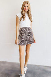 Image of model wearing the NATION LTD Birdie Skirt, standing infront of white wall, full body front view