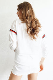 Image of model wearing SUNDAYS Reggie Popover Top standing against white wall back view looking over left shoulder