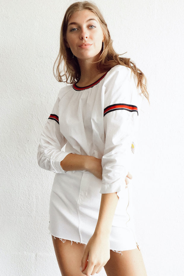 Image of model wearing SUNDAYS Reggie Popover Top standing against white wall front view, with one arm bent across body
