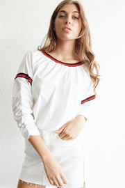 Image of model wearing SUNDAYS Reggie Popover Top standing against white wall, front view with one hand in pocket