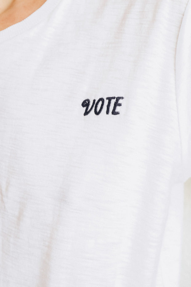Image of model wearing the NATION LTD Vote Tee standing infront of white wall, front view close up